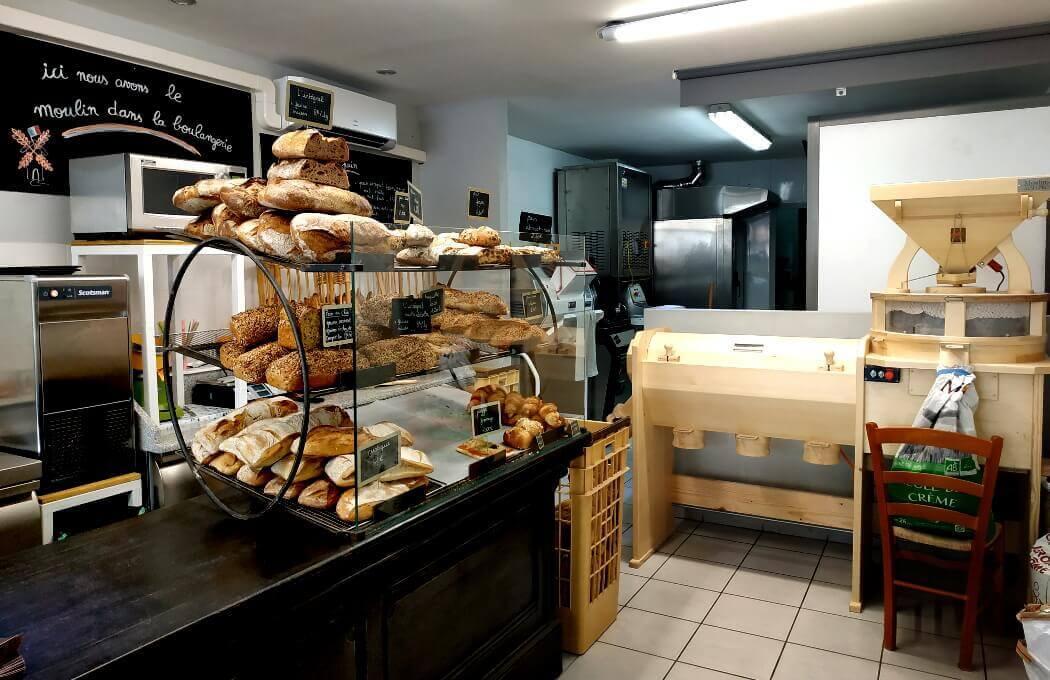 Un moulin à meules dans une boulangerie pour produire des farines de qualité et confectionner des pains d'exception